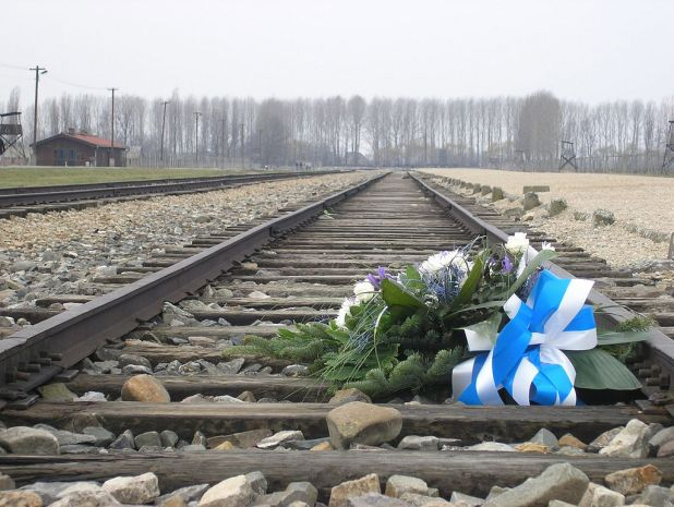 Photo of train tracks leading away from the Auschwitz-Birkenau concentration and death camps; flowers bound in a white-and-blue striped ribbon have been placed on the tracks.