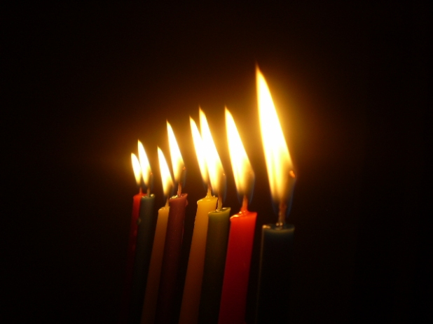 Eight colorful Hanukkah candles, lit, against a dark background
