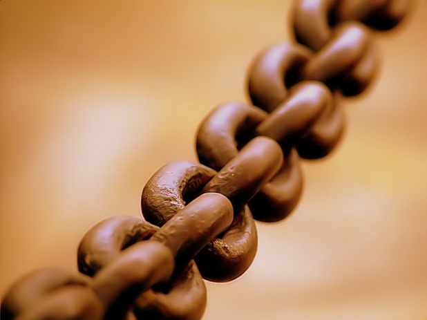 Close-up photograph of an iron chain running from the lower-left to the upper-right corners of the frame